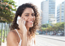 Latin woman in the city flirting at phone Stock Photo
