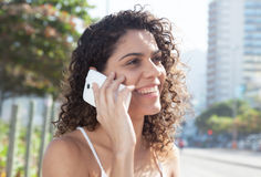 Latin woman in the city speaking at phone. With modern buildings and trees in the background Stock Image