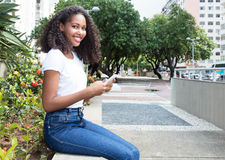 Latin woman with curly hair sending message with phone Stock Photos