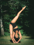 Latin woman dancer doing a handstand with one leg. In a forest Royalty Free Stock Image