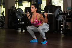 Latin Woman Doing Exercise Barbell Squat. Young Mexican Woman Working Out Legs With Barbell In Fitness Center - Squat Stock Image
