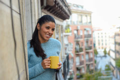 Latin woman drinking cup of coffee or tea smiling happy at apartment window balcony Stock Photos