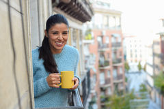Latin woman drinking cup of coffee or tea smiling happy at apartment window balcony Stock Images