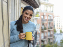 Latin woman drinking cup of coffee or tea smiling happy at apartment window balcony Stock Image