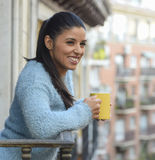 Latin woman drinking cup of coffee or tea smiling happy at apartment window balcony Stock Photo