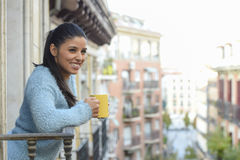 Latin woman drinking cup of coffee or tea smiling happy at apartment window balcony Royalty Free Stock Photos
