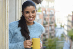 Latin woman drinking cup of coffee or tea smiling happy at apartment window balcony. Young beautiful latin woman drinking cup of coffee or tea holding the mug Royalty Free Stock Images