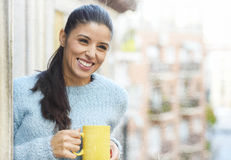 Latin woman drinking cup of coffee or tea smiling happy at the apartment window balcony Stock Images