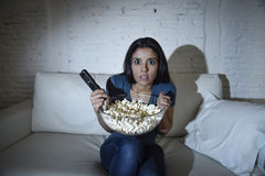Latin woman at home sofa couch in living room watching television covering eyes horrified Royalty Free Stock Photos