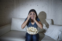 Latin woman at home sofa couch in living room watching television covering eyes horrified Stock Photography