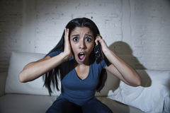 Latin woman at home sofa couch in living room watching television scary horror movie or suspense thriller Stock Image