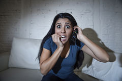 Latin woman at home sofa couch in living room watching television scary horror movie or suspense thriller. Young hispanic woman at home sofa couch in living room royalty free stock image
