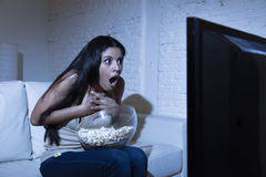 Latin woman at home sofa couch in living room watching television scary horror movie or suspense thriller Royalty Free Stock Image