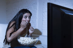 Latin woman at home sofa couch in living room watching television scary horror movie or suspense thriller. Young Spanish woman at home sofa couch in living room Stock Photos