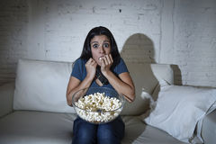 Latin woman at home sofa couch in living room watching tv covering eyes horrified Royalty Free Stock Photo