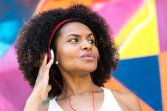 Latin woman listing to music on colorful background Royalty Free Stock Photo