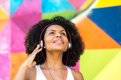Latin woman listing to music on colorful background Stock Photography