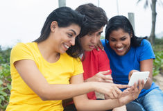 Latin woman looking selfies at phone with caucasian man and native girl Stock Photography