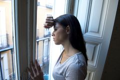 Latin woman lying at home looking through window frustrated suffering depression. Young attractive latin woman lying at home looking through window frustrated stock photography