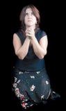 Latin woman praying and holding a small crucifix Royalty Free Stock Photo