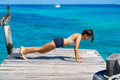 Latin woman push up workout in beach pier Royalty Free Stock Photos