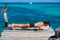 Latin woman push up workout in beach pier Stock Photography