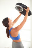 Latin woman raising a weight scale. Latin woman in sports clothing raising a weight scale Royalty Free Stock Images