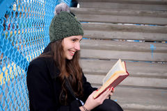 Latin woman reading on the stairs of the train station Royalty Free Stock Image