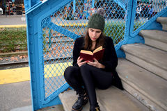 Latin woman reading on the stairs of the train station Stock Photography