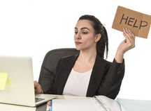 Latin woman showing help sign desperate suffering stress at work while sitting at office laptop. Young attractive latin woman showing help sign desperate Royalty Free Stock Photography