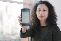 Woman with phone. Latin woman showing us a mobile phone Royalty Free Stock Photo