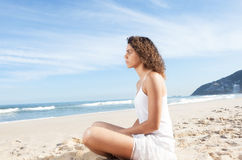 Latin woman sitting at beach and looking to the ocean Stock Photos