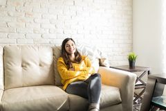 Latin Woman Sitting At Home. Portrait of woman in cozy yellow sweater with confident look resting on sofa at home stock photo