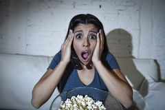 Latin woman sitting at home sofa couch in living room watching television scary horror movie Royalty Free Stock Images