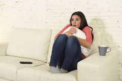 Latin woman sitting at home sofa couch in living room watching television scary horror movie. Young beautiful latin woman sitting at home sofa couch in living Stock Image