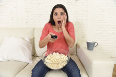 Latin woman sitting at home sofa couch in living room watching television scary horror movie Stock Photos
