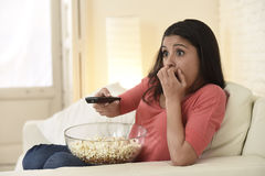 Latin woman sitting at home sofa couch in living room watching television scary horror movie Royalty Free Stock Photography