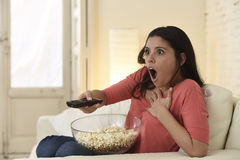 Latin woman sitting at home sofa couch in living room watching television scary horror movie Stock Image