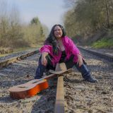 Latin woman sitting on railroad tracks with jeans, a black blouse, a pink shawl, a brown hat and a guitar. Beautiful latin woman sitting on railroad tracks with royalty free stock photography