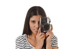 Latin woman taking pictures looking through the viewfinder of an old cool retro vintage photo camera Royalty Free Stock Photography