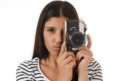 Latin woman taking pictures looking through the viewfinder of an old cool retro vintage photo camera Royalty Free Stock Photo