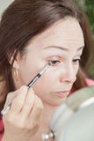 Latin woman using make up Stock Images