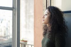 Woman at the window. Latin woman watching through her home window Royalty Free Stock Images
