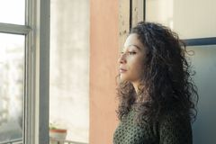Woman at the window. Latin woman watching through her home window Stock Photos