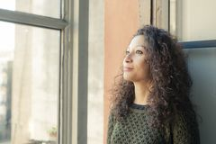 Woman at the window. Latin woman watching through her home window Royalty Free Stock Photography