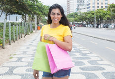 Latin woman with yellow shirt and shopping bags in city Royalty Free Stock Image
