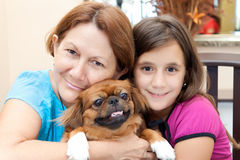 Latin women with their family dog. Grandmother and granddaughter hugging the family dog Stock Image