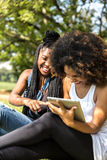 Latin women using tablet computer in the park Stock Photo