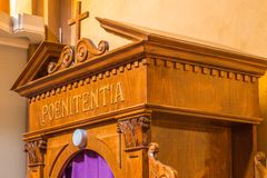 Latin word on a wooden confessional. The Latin word poenitentia meaning repentance Stock Photos