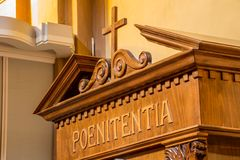 Latin word on a wooden confessional. The Latin word poenitentia meaning repentance Stock Photography
